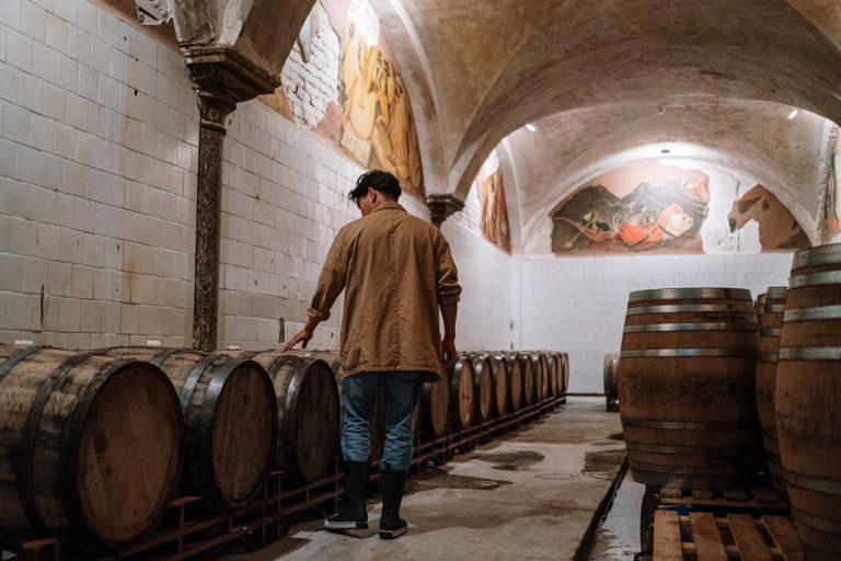 man and wine barrels